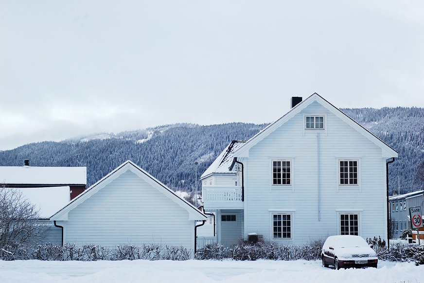 Hvit enebolig på vinteren med snø på taket