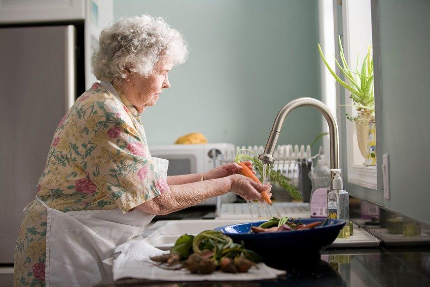 Eldre kvinne vasker grønnsaker i kjøkkenvask