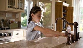 Ung jente vasker hendene i kjøkkenvask