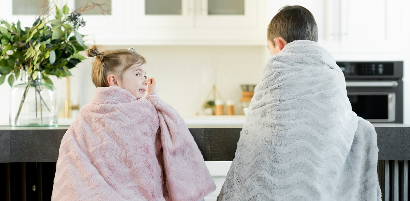 To barn under pledd på stoler ved kjøkkenbenken