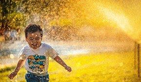 Barn som løper gjennom spreder på en sommerdag