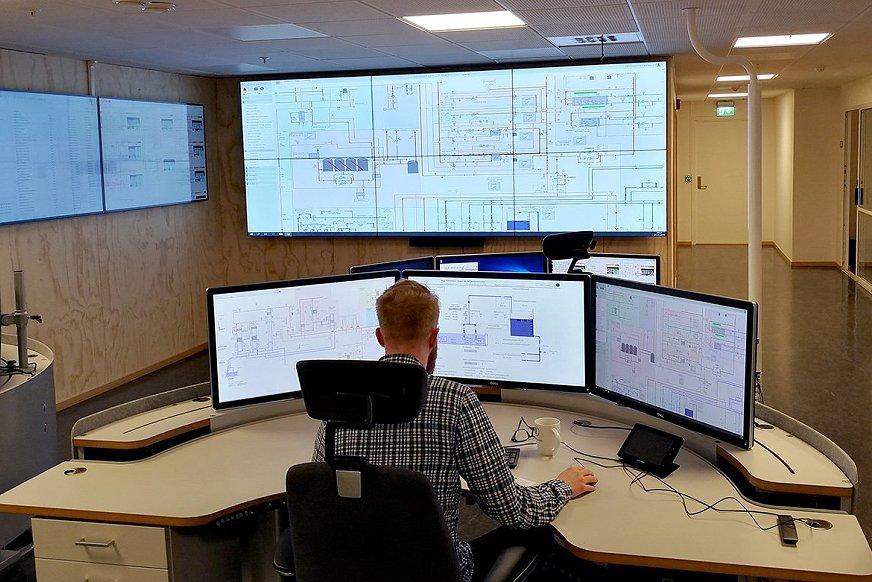 Mann sitter ved skjermer ved Universitetet i Bergen sin nye driftssentral